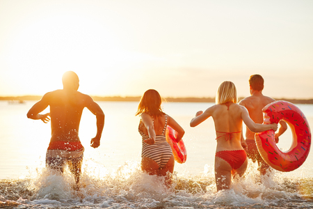 Rearview of a diverse group of young friends in swimsuits splashing water while running into a lake together at sunset