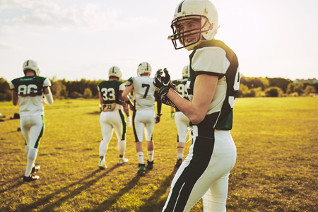 Confident young quarterback walking on a field on a sunny afternoon with a group of young American football players during a practice game Stock Photo - 103529487