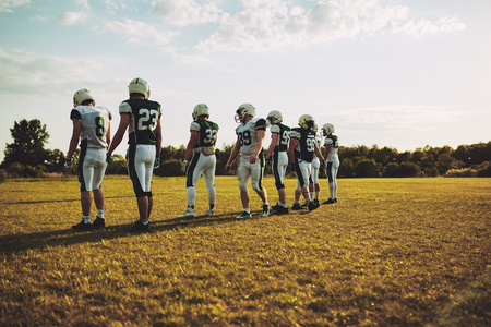 Group of young American football players standing in a row together during a practice session on a grassy field in the afternoon Stock Photo