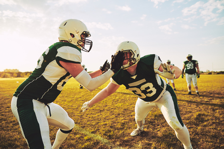 Group of young American football players doing tackling drills during a practice session on a grassy field on a sunny afternoon Stock Photo - 103529498