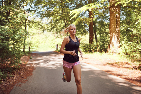Fit young blonde woman in shorts and a tanktop running alone along a path through a forest