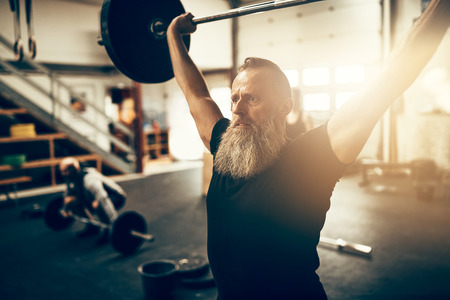 Fit mature man with a beard holding heavy weights over his head during a workout session in a gym 스톡 콘텐츠