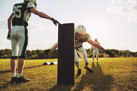 Group of young American football players practicing tackles and defensive drills outside together on a grassy field in the afternoon Stock Photo