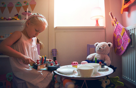 Little girl with plastic toy cake playing tea-party with bear. Horizontal indoors shot. Foto de archivo - 104030773
