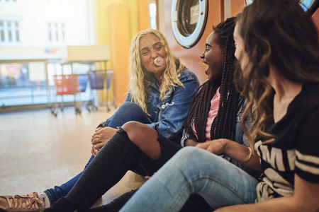 Group of young friends sitting on a laundromat floor together laughing and blowing bubbles with chewing gum Banco de Imagens