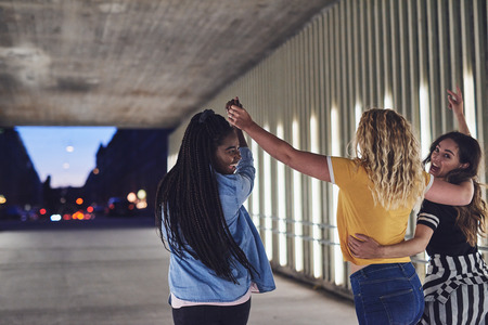 Rearview of a group of young girlfriends having fun while walking together down a walkway in the city at night Banco de Imagens