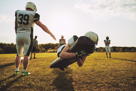 Group of young American football players practicing defence and tackles outside together on a grassy field in the afternoon Stock Photo - 104031035