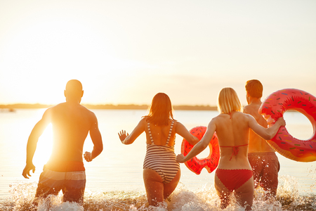 Rearview of a group of diverse young friends in swimsuits splashing water while running together into a lake at sunset