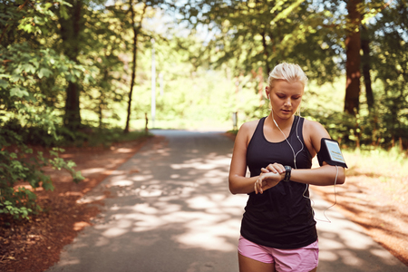 Fit young woman in sportswear standing in the middle of a forest path checking her sports watch before going for a run Reklamní fotografie