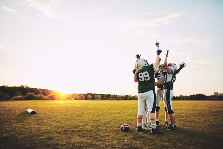 Ecstatic group of American football players standing in a huddle and raising a championship trophy in celebration Reklamní fotografie
