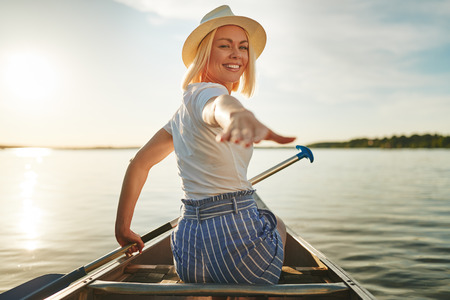 Smiling young woman looking back over her shoulder and reaching out her hand while canoeing on a lake on a sunny summer afternoon