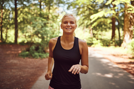 Fit young blonde woman in shorts and a tanktop smiling while running alone along a path through a forest Stock Photo