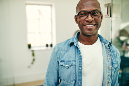 Young African businessman wearing glasses and smiling while leaning against a glass wall in a modern office