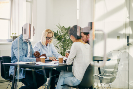 Diverso grupo de jóvenes empresarios sentados alrededor de una mesa dentro de una sala de juntas con paredes de vidrio tener una reunión juntos Foto de archivo - 105356039