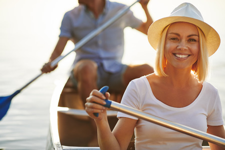 Smiling young woman paddling a canoe with her boyfriend on a tranquil lake on a late summer afternoon