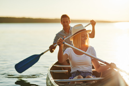 Smiling young couple paddling a canoe on a scenic lake on a sunny summer day Stok Fotoğraf