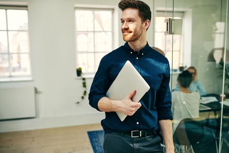 Lächelnder junger Geschäftsmann, der mit seinem Laptop in einem modernen Büro mit Arbeitskollegen im Hintergrund geht