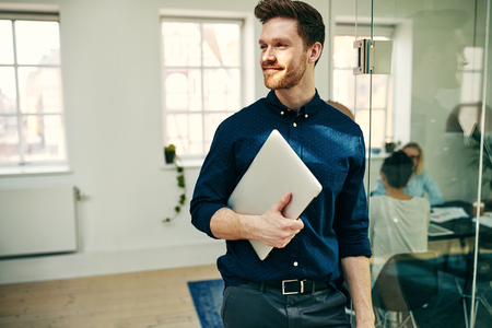 Sorridente giovane uomo d'affari che cammina con il suo laptop in un ufficio moderno con i colleghi al lavoro in background