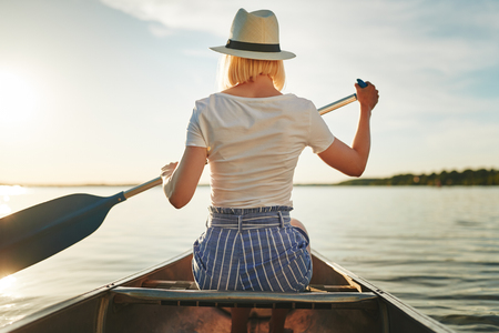 Rearview of a young woman looking at the view while paddling a canoe on a still lake on a late summer afternoon Stock Photo