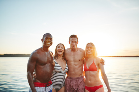 Diverse group of a smiling young friends in swimwear standing arm in arm together in a lake on a late summer afternoon 写真素材