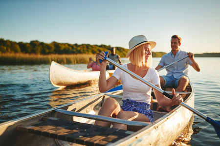 Young woman laughing while paddling a canoe on a lake with her boyfriend and another couple on a sunny summer afternoon 스톡 콘텐츠