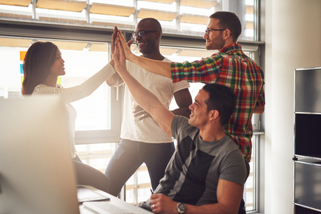 Group of four diverse men and women in casual clothing celebrating business accomplishments in office near desk and bright window