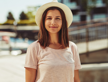 Smiling young woman enjoying a sunny summer day while standing alone outside wearing a hat 写真素材