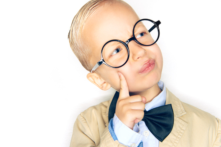 Adorable little blonde boy wearing a suit, bowtie and glasses looking deep in thought while standing against a white background