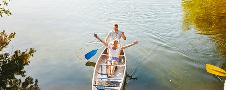 Smiling young woman leaning back on her boyfriend and enjoying nature and fresh air while canoeing on a lake Stock Photo