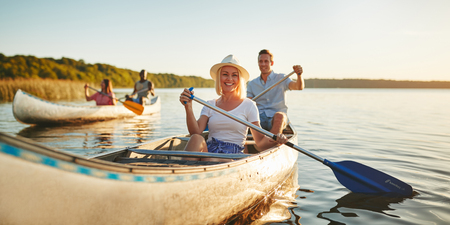 Young woman smiling while paddling a canoe on a lake with her boyfriend and another couple on a sunny afternoon in summer