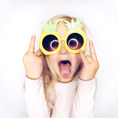 Adorable little girl with long blonde hair wearing funny pineapple sunglasses sticking out her tongue and make rude gestures against a white background