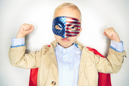 Cute little boy superhero in a suit and bowtie wearing a red cape and stars and stripes mask flexing his muscles against a white background