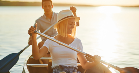 Smiling young woman paddling a canoe with her boyfriend on a lake on a sunny summer afternoon
