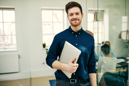 Young businessman smiling confidently while standing in a modern office holding his laptop with colleagues at work in the background