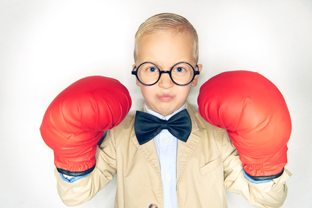 Cute little boy in a suit and bowtie wearing oversize boxing gloves and looking fearless while standing against a white background