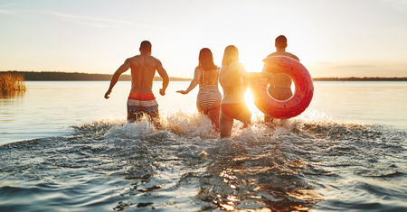 Rearview of a group of diverse young friends in swimsuits splashing water while running into a lake together on a late summer afternoon