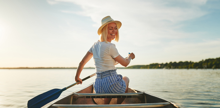 Young woman looking back over her shoulder and smiling while paddling a canoe on a lake on a late summer afternoon