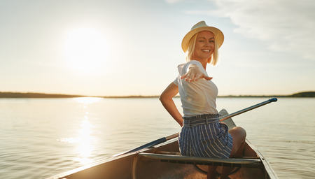 Smiling young woman looking back over her shoulder and reaching out with her hand while paddling a canoe on a lake in summer