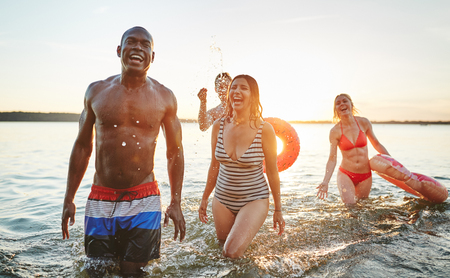 Laughing group of diverse young friends in swimwear having fun together in a lake on a late summer afternoon Stockfoto