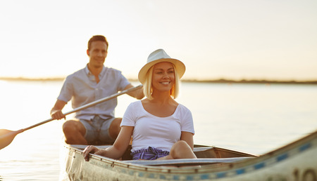 Smiling young couple enjoying a sunny day paddling a canoe together on a lake on a summer afternoon