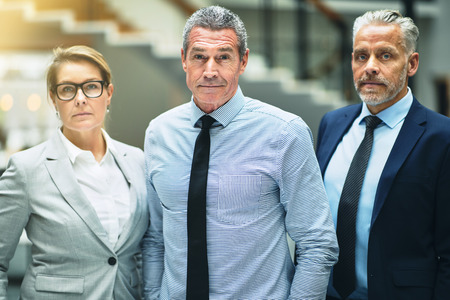 Confident mature businessman standing with two work colleagues in the lobby of a modern office building Stock Photo - 106891077