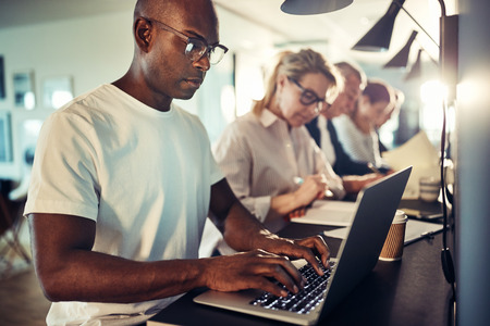Young African designer focused on his work while sitting in a row with colleagues at a table in a modern office Stok Fotoğraf