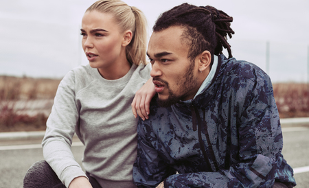Diverse young couple in sportswear crouching on a road taking a break from a run together outdoors on an overcast day