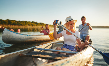 Young woman smiling while paddling a canoe on a scenic lake with a group of friends on a sunny summer afternoon Stock Photo