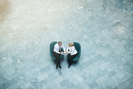 High angle of two mature businesspeople sitting on chairs in an office lobby discussing work together and using a digital tablet