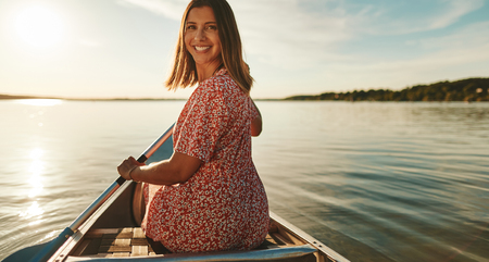 Smiling young woman looking back over her shoulder while paddling a canoe on a lake on a late summer afternoon