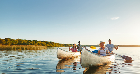 Two smiling young couples paddling canoes together on a still lake on a sunny summer afternoon