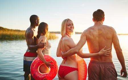 Smiling woman in a bikini looking over her shoulder while standing with her boyfriend and another couple in a lake watching the sunset