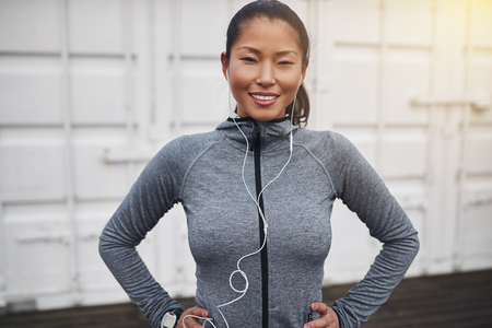 Smiling young Asian woman in sportswear wearing earphones and standing with her hands on her hips outdoors before a run