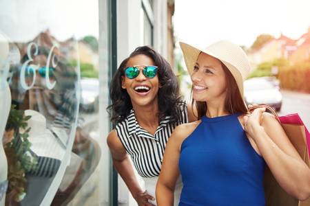 Excited and beautiful enthusiastic friends window shopping together outside during the summer